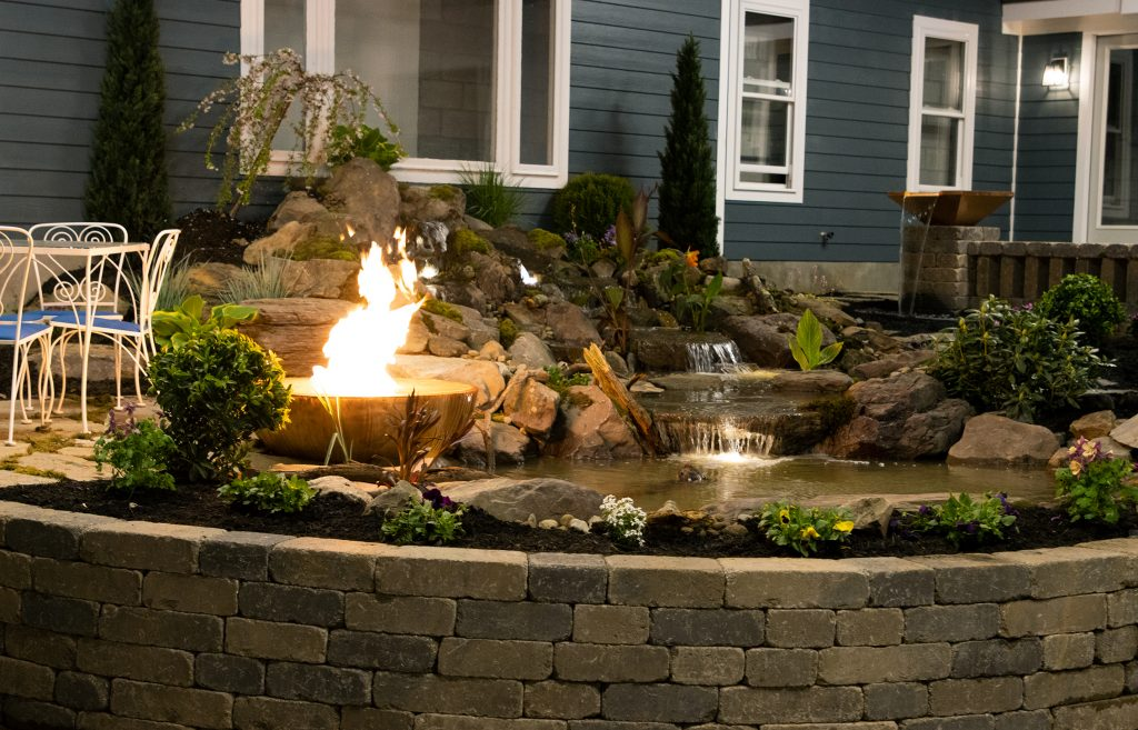 Pond and waterfall with a Copper Fountain Bowl and fire feature flowing into the pond