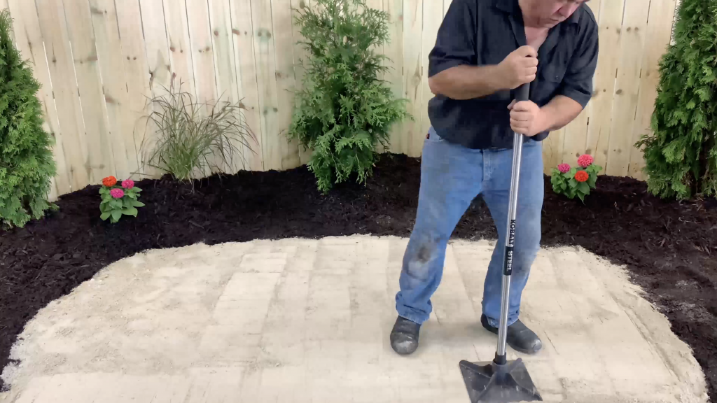 Man tamping out sand for water feature base