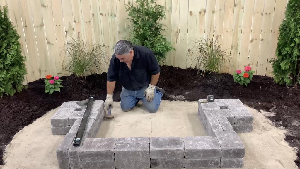 Man building the stone base of a hardscape reservoir basin