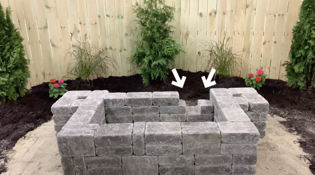 Arrows pointing to a spot in the wall of a hardscape reservoir stone basin to show where the plumbing will go