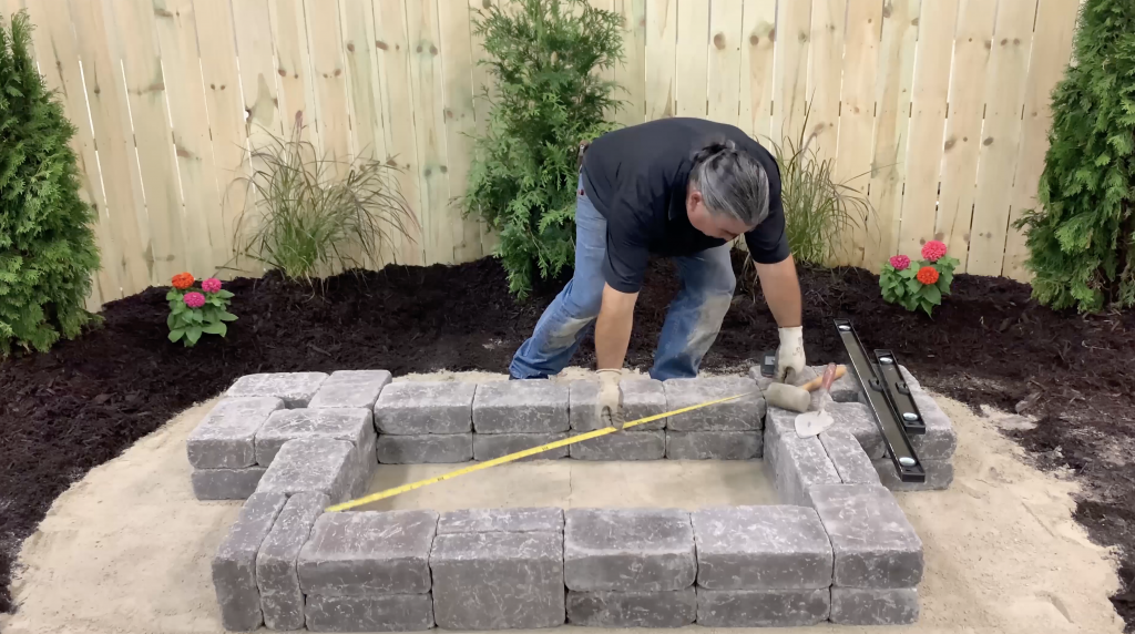 Man measuring the corners of the base of a hardscape reservoir basin