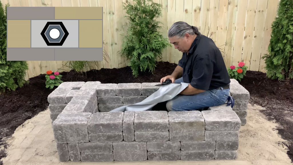 Man installing a bulkhead fitting to a hardscape flexible basin liner