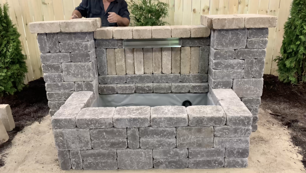 Man building a stone hardscape basin for a Stainless Steel Spillway water feature