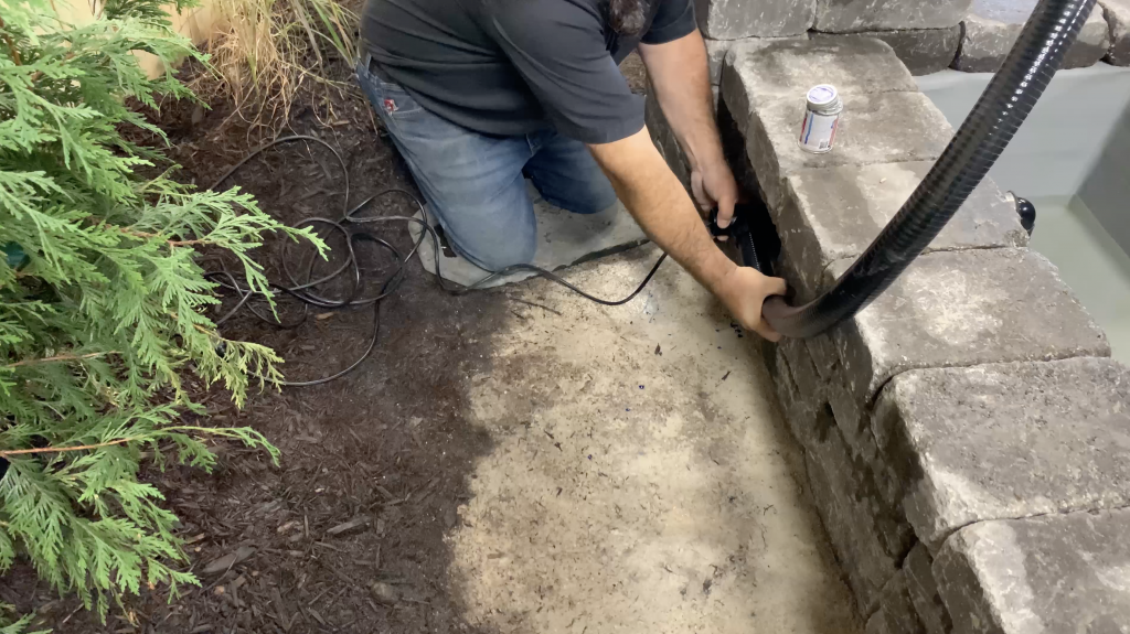 Man installing the pipe for the back plumbing of a Copper Spillway Bowl hardscape water feature