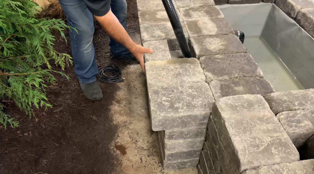 Man finishing building the back wall to conceal the plumbing of a Copper Spillway Bowl hardscape water feature