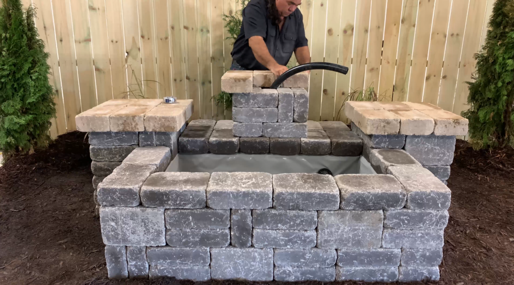 Man building stone columns for a Copper Spillway Bowl hardscape water feature