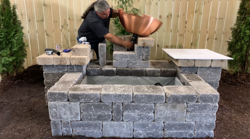 Man placing a copper bowl on top of a stone hardscape column for a Copper Spillway Bowl water feature
