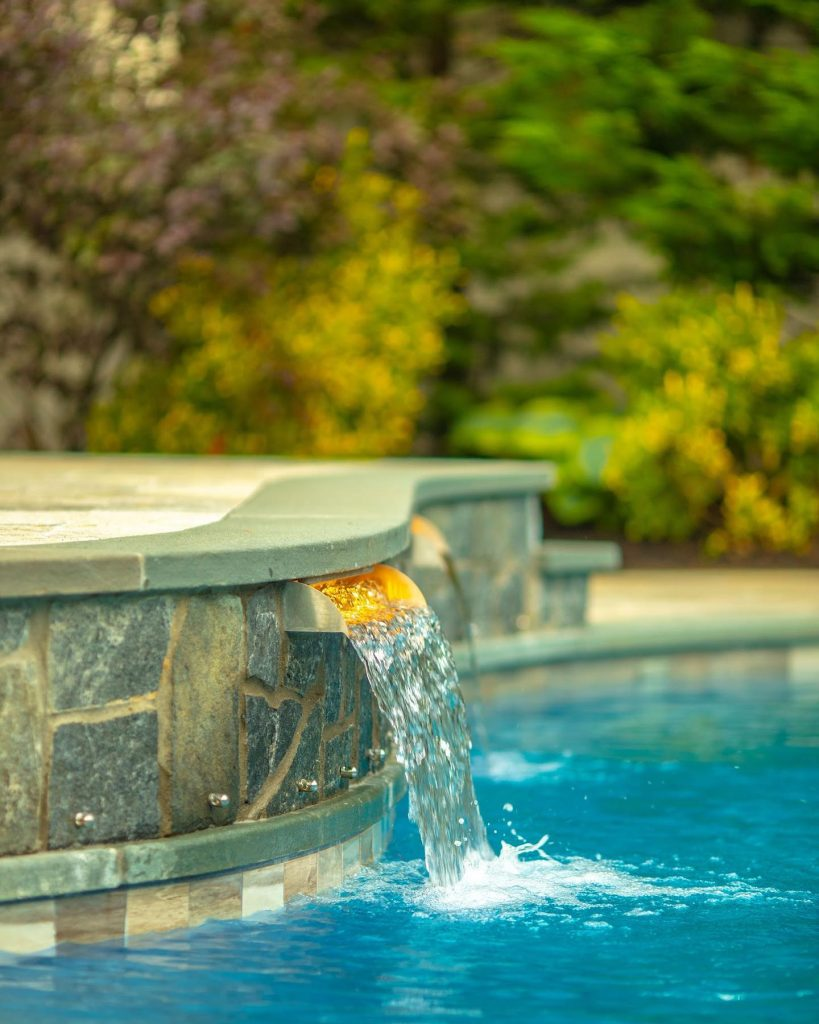 Pool with Stainless Steel Spillway flowing water into it by Designing with Elements