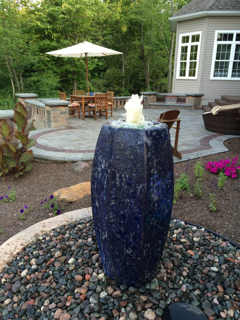 Blue Fountain Vase in a backyard with a patio