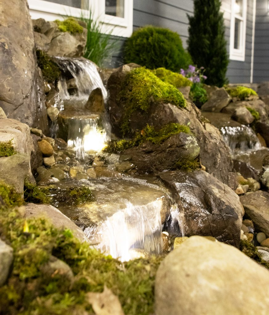 Rock waterfall on the side of a house with waterfall lights