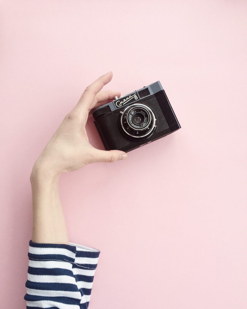 hand holding a camera against a pink background