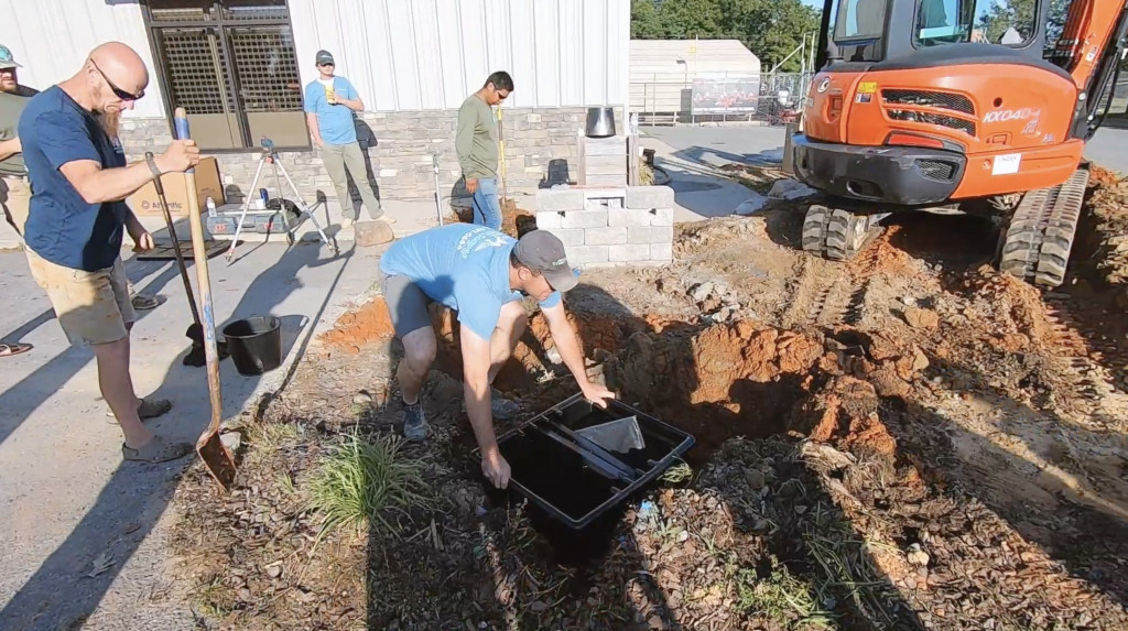 Contractor installing a skimmer into the side of a pond