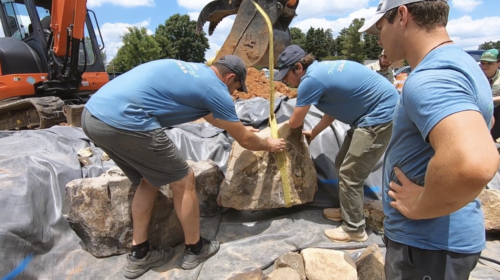 Two men placing framing rocks for a waterfall