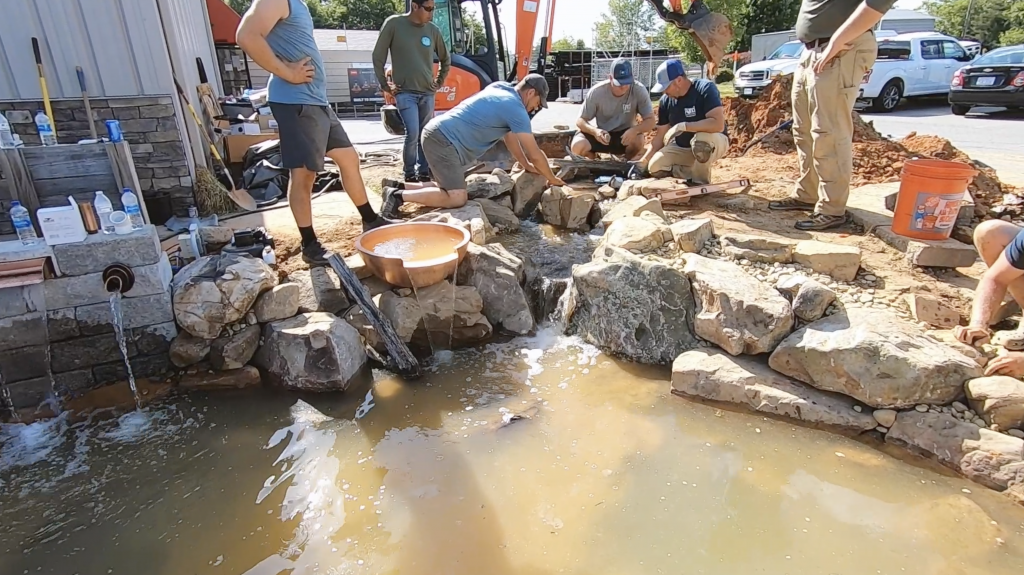 Men creating a waterfall into a pond