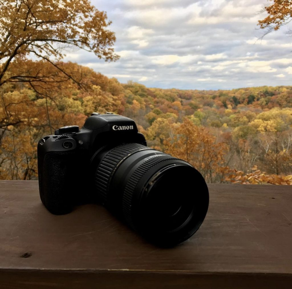 Canon Camera sitting on a wood railing looking out at a fall day in the woods
