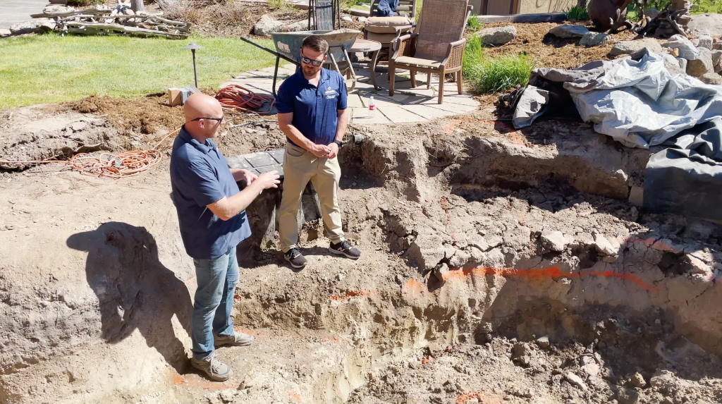 Contractors standing in a dug out pond showing how to create a trench to move ground water from underneath the pond liner