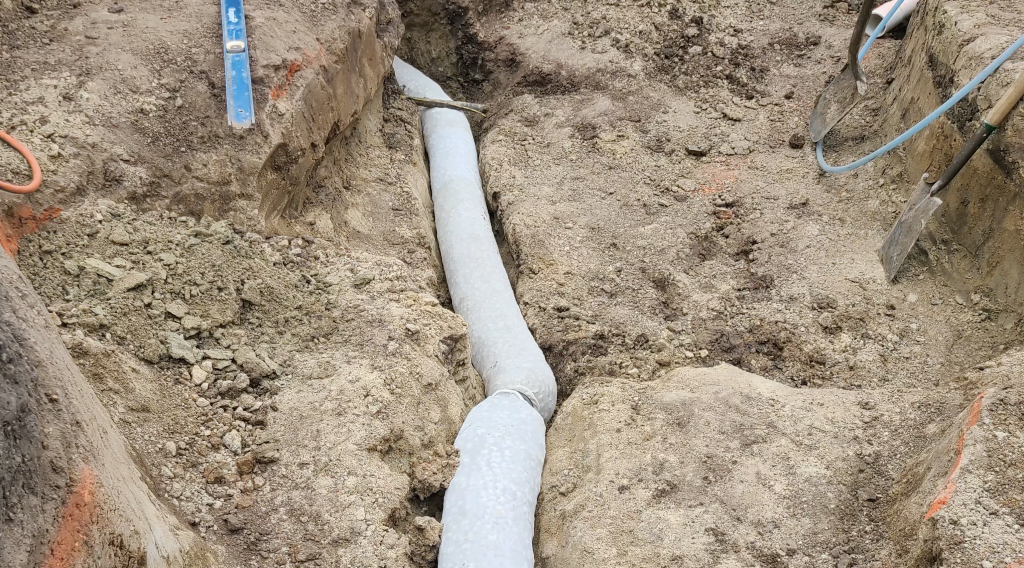 French drain trench to help move ground water from under a pond liner